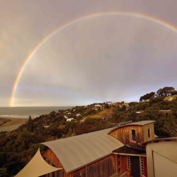 A full double rainbow stretches over Heavenly Spot Homestay